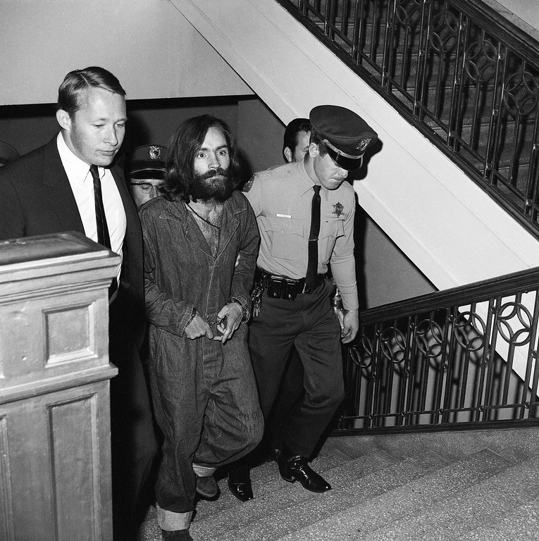 ". Charles M. Manson, 35-year-old bearded leader of a communal clan he calls ""the family\"" is shown as he arrived in Los Angeles, Dec. 10, 1969, to be jailed on murder-conspiracy charges in the deaths of actress Sharon Tate and six others. His arraignment is scheduled for Thursday. Three women indicted with him by a Los Angeles County grand jury Monday will appear for arraignment. (AP Photo/Harold P. Matosian)"