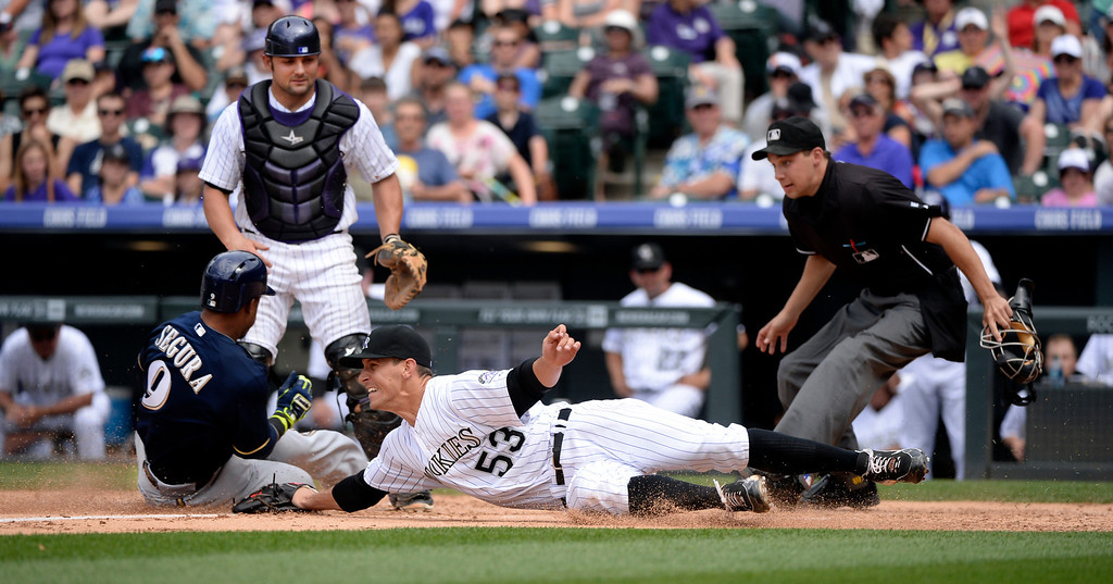 . DENVER, CO - JUNE 21: Colorado pitcher Christian Friedrich missed the tag on Milwaukee baserunner Jean Segura as he crossed the plate in the third inning. The Brewers cleared the bases on a wild pitch and an error. The Colorado Rockies hosted the Milwaukee Brewers at Coors Field Saturday afternoon, June 21, 2014. Photo by Karl Gehring/The Denver Post
