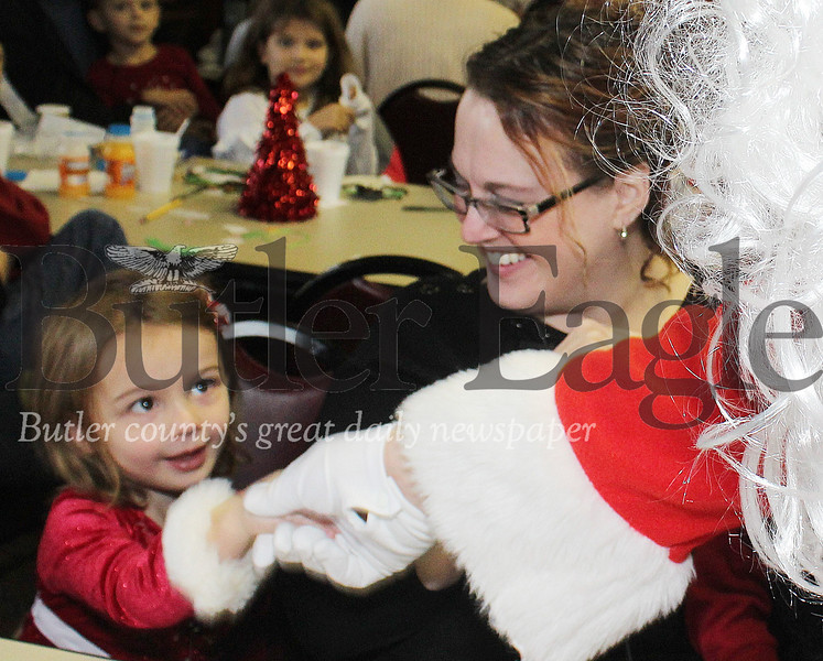 Harold Aughton/Special to the Eagle: Janet Zak watches as her daughter Casey 3, of Renfrew receives a very special handshake from Santa Saturday morning at the Butler Twp. Parks & Recreation Building.