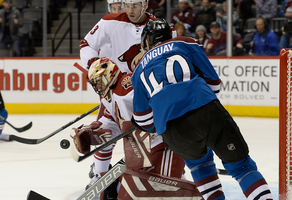 . DENVER, CO - FEBRUARY 16: Colorado Avalanche left wing Alex Tanguay (40) takes a swipe a the puck with this stick as Arizona Coyotes goalie Mike McKenna (43) knocks it away during the first period February 16, 2015 at Pepsi Center. (Photo By John Leyba/The Denver Post)