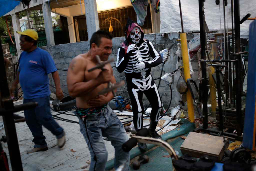 """. In this April 23, 2016 photo, members of the Lucha Libre wrestling group who call themselves, \""""Guerreros del Cuadrilatero-Club Soley\""""or Club Soley Wing Warriors, train for a show on the back patio of a barbershop in the Las Cruces neighborhood of Acapulco, Mexico. Residents of Acapulcoís slums suffer the worst of the violence despite the high-profile tourist-quarter killings. New police chief Max Saldana said he thinks the gangs ìhave retreated up into the ëcolonias,íî or slums, where few tourist dollars ever arrive. (AP Photo/Enric Marti)"""