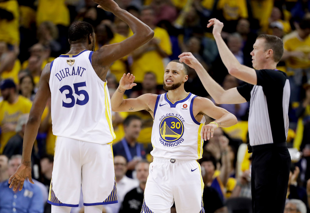 . Golden State Warriors forward Kevin Durant (35) celebrates with guard Stephen Curry (30) during the second half of Game 1 of basketball\'s NBA Finals against the Cleveland Cavaliers in Oakland, Calif., Thursday, May 31, 2018. (AP Photo/Marcio Jose Sanchez)