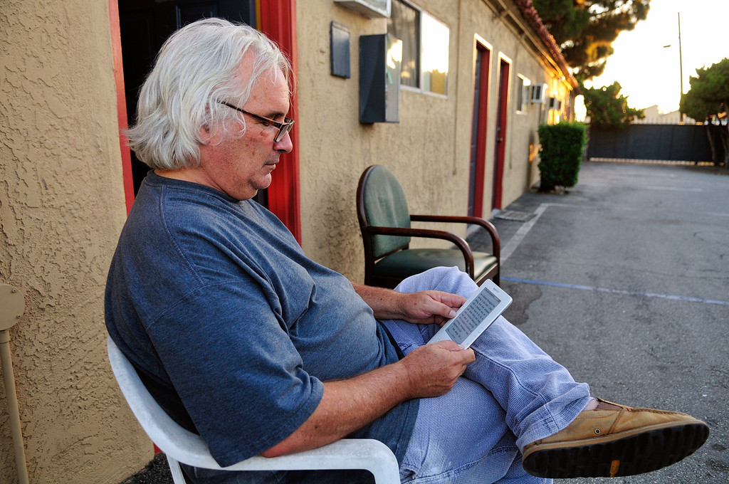 . The sun begins to set on the El Capitan Motor Inn as Tim Grobaty reads his Kindle outside his room.Photo by Thomas Wasper for the Press Telegram