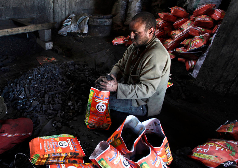 . A Palestinian worker fills bags with coal to be sold, in Jabalya refugee camp in the north of the Gaza Strip on March 24, 2013. In adapting to years of border blockades and shortages, Gazans have become experts at recycling and making new out of old including turning scrap wood into charcoal to be used for barbecue grills and water pipes in local restaurants and coffee houses. (AP Photo/Hatem Moussa)