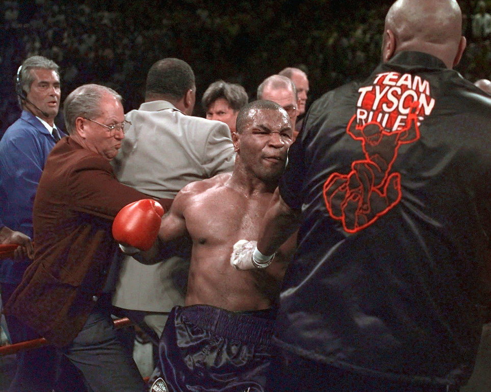 . FILE---Mike Tyson continues to battle in the ring after his fight against Evander Holyfield was stopped after Tyson bit Holyfield on the ear, in the third round of their WBA Heavyweight match Saturday, June 28, 1997, at the MGM Grand in Las Vegas. Thursday July 9, 1997, Tyson\'s boxing license was revoked  and he was fined the maximum $3 million for the incident.  Tyson, who also was ordered to pay legal costs, can apply for reinstatement of his license in one year. (AP Photo/Mark J. Terrill)