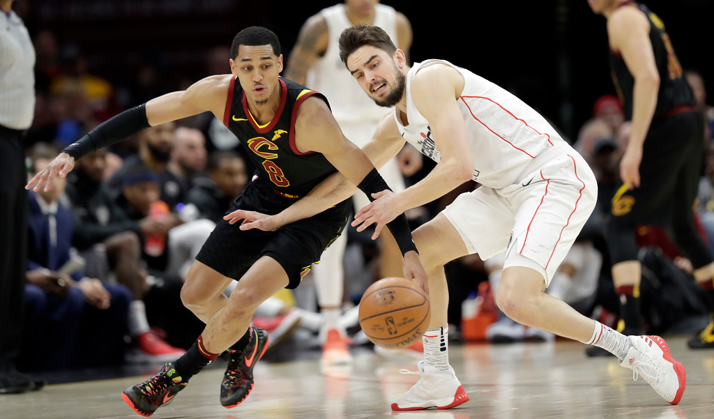 . Cleveland Cavaliers\' Jordan Clarkson, left, and Washington Wizards\' Tomas Satoransky, from Czech Republic, battle for a loose ball in the first half of an NBA basketball game, Thursday, April 5, 2018, in Cleveland. (AP Photo/Tony Dejak)