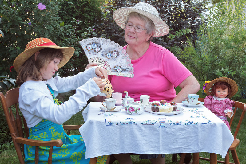 Grandmother and little girl having a garden tea party