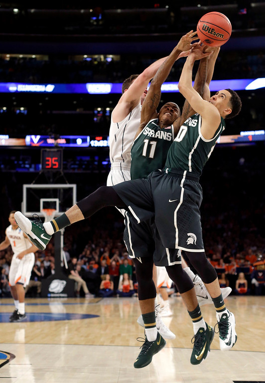 . Michigan State guards Keith Appling, center, and Travis Trice, right, compete for the ball with Virginia guard Joe Harris during the first half in a regional semifinal of the NCAA men\'s college basketball tournament, Friday, March 28, 2014, in New York. (AP Photo/Frank Franklin II)