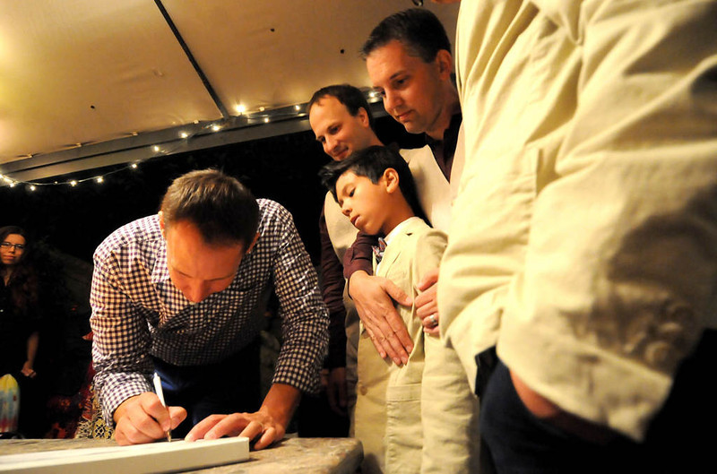 . Bradley Weber, back middle, and husband Ryan Pfeifle, top middle, and son Josh Pfeifle-Weber, 11, watch as witness and best man Bruce Maeder,left, signs legal documents of their marriage after the wedding on August 1, 2013. (Pioneer Press: Sherri LaRose-Chiglo)