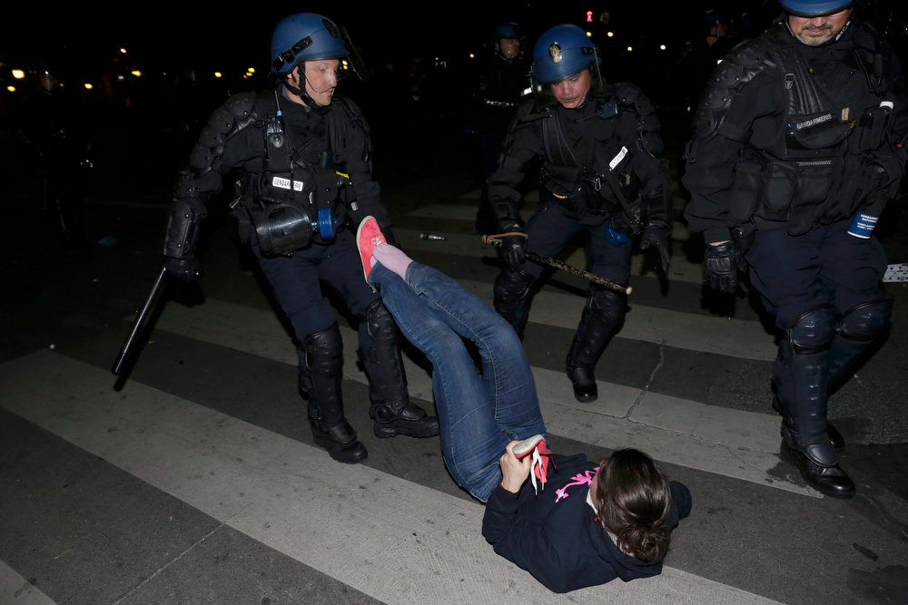 """. French gendarmes apprehend a demonstrator during clashes at the end of the \""""La Manif pour Tous\"""" (Demonstration for All) to protest against France\'s legalization of same-sex marriage, in Paris, early April 24, 2013. French parliament approved a law allowing same-sex couples to marry and to adopt children on Tuesday, a flagship reform pledge by French President which sparked often violent street protests and a rise in homophobic attacks. The law legalizes gay marriage and gives gay and lesbian couples adoption rights.     REUTERS/Philippe Wojazer"""