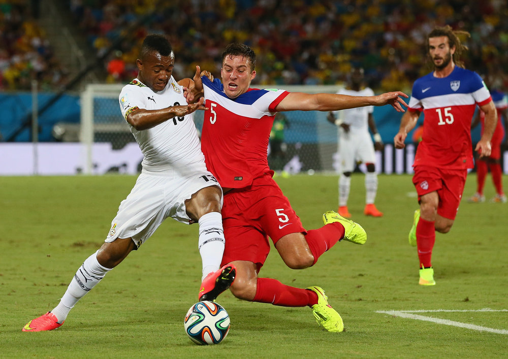 Description of . Matt Besler of the United States challenges Jordan Ayew of Ghana during the 2014 FIFA World Cup Brazil Group G match between Ghana and the United States at Estadio das Dunas on June 16, 2014 in Natal, Brazil.  (Photo by Kevin C. Cox/Getty Images)