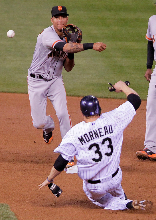 . San Francisco Giants\' Ehire Adrianza, top, throws to first for a double play over the head of Colorado Rockies\' Justin Morneau, bottom, during the fourth inning of a baseball game, Tuesday, April 22, 2014, in Denver. (AP Photo/Barry Gutierrez)
