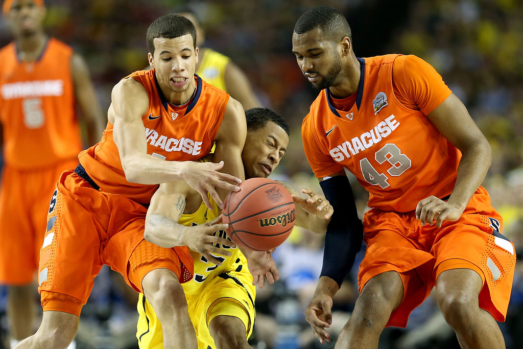 . ATLANTA, GA - APRIL 06:  Trey Burke #3 of the Michigan Wolverines attempts to control the ball in the first half against Michael Carter-Williams #1 and James Southerland #43 of the Syracuse Orange during the 2013 NCAA Men\'s Final Four Semifinal at the Georgia Dome on April 6, 2013 in Atlanta, Georgia.  (Photo by Streeter Lecka/Getty Images)