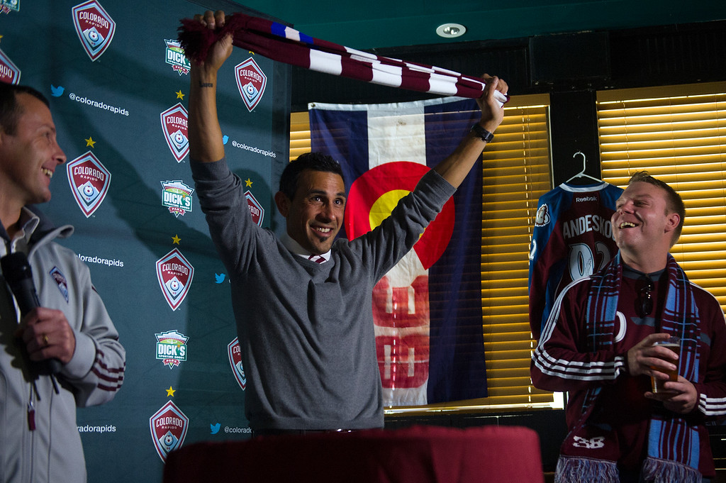 . Former Colorado Raids player and captain Pablo Mastroeni holds a Rapids scarf above is head with fans surrounding him after he was named the team\'s new head coach at the Celtic Tavern on March 8, 2014, in Denver, Colorado. (Photo by Daniel Petty/The Denver Post)