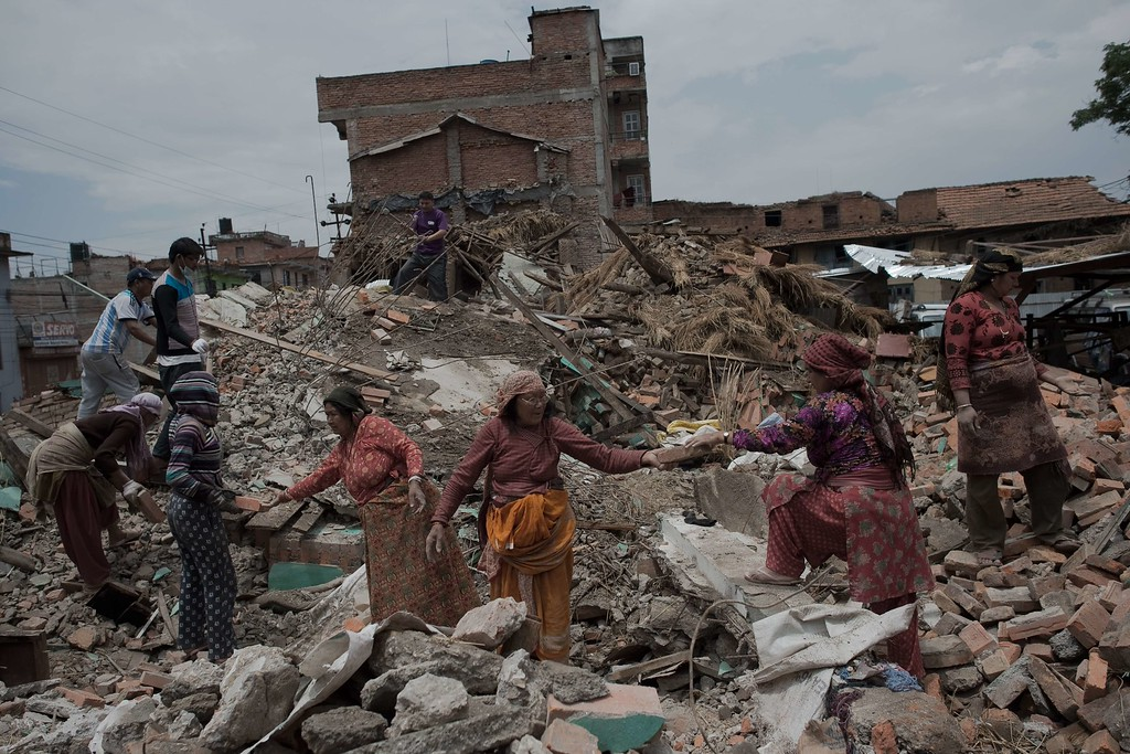 . Residents clear the rubble of their destroyed houses in Harisddhi on the outskirts of the Nepalese capital Kathmandu on April 29, 2015, following a 7.8 magnitude earthquake which struck the Himalayan nation on April 25. Rescuers are facing a race against time to find survivors of a mammoth earthquake that killed more than 5,000 people when it through Nepal five days ago and devastated large parts of one of Asia\'s poorest nations. AFP PHOTO / Nicolas  ASFOURI/AFP/Getty Images