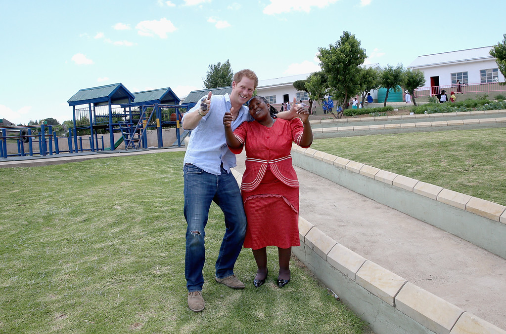 ". Prince Harry gives a thumbs up with Head Teacher of the Thuso Centre Mamonuku Mofilikoane in front of a playground and path he helped build in 2008 during a visit with the a group of soldiers from the British Army on December 7, 2014 in Bute-Bute, Lesotho. Prince Harry was visiting Lesotho to see the work of his charity Sentebale. Sentebale provides healthcare and education to vulnerable children in Lesotho, Southern Africa. Prince Harry said ""The playground and ramps in this photo were made by 30 members of the British Army. Blood, sweat and tears went into the project over two weeks. The whole place looks incredible, the children are all smiles. Thanks lads.\"" (Photo by Chris Jackson - WPA Pool /Getty Images)"