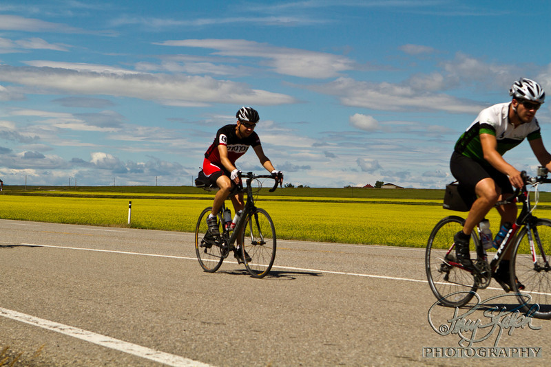 Maple Expedition Bike Tour - Day X:  A to B.  Jeremy and Jack riding in Canola Fields