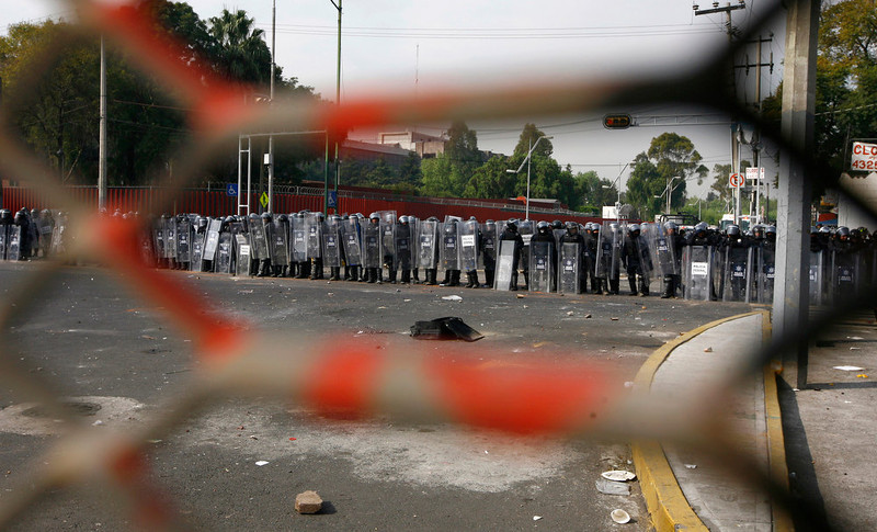 """. Mexican federal police in riot gear are seen through openings of a steel barrier outside the National Congress, just hours before Mexico\'s new president was to take the oath of office in Mexico City, Saturday, Dec. 1, 2012.   Hundreds of protesters  opposed to new Mexican President Enrique Pena Nieto banged on the steel security barriers around Congress, threw rocks, bottle rockets and firecrackers at police and yelled \""""Mexico without PRI!\""""  Pena Nieto took power at midnight in a symbolic ceremony and formally took the oath of office Saturday morning in congressional chambers. (AP Photo/Marco Ugarte)"""