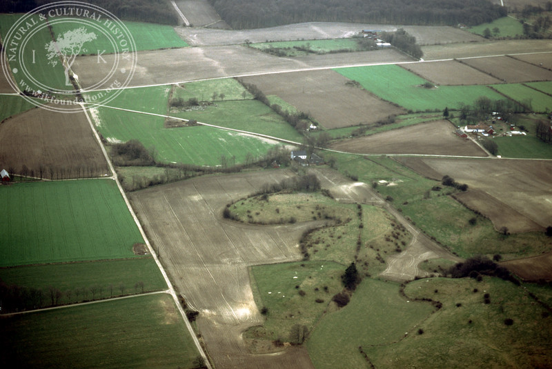 Farmland west of Ravlunda church - with plantations, buildings and prehistoric remains (Lingers kulle) (2 April, 1989). | LH.0480