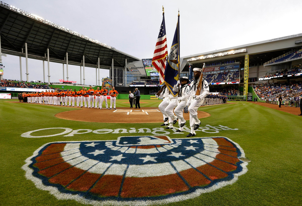 . The color guard matches onto the field during a pre-game ceremony for opening night baseball game between the Miami Marlins and Colorado Rockies, Monday, March 31, 2014, in Miami. (AP Photo/Lynne Sladky)