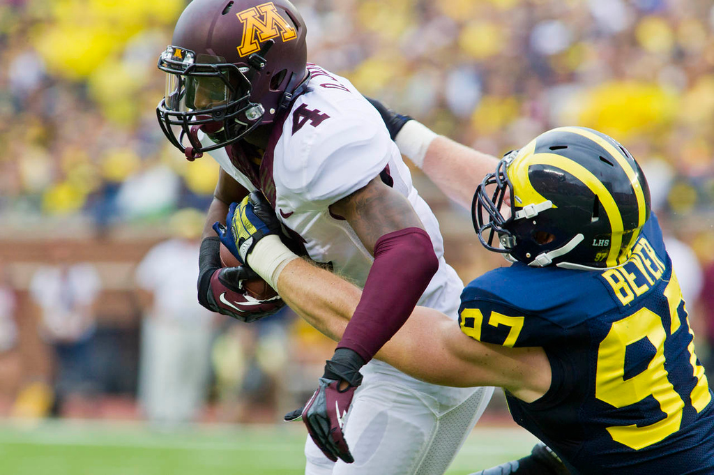 . Minnesota wide receiver Donovahn Jones tries to break a tackle from Michigan linebacker Brennen Beyer in the first quarter. (AP Photo/Tony Ding)