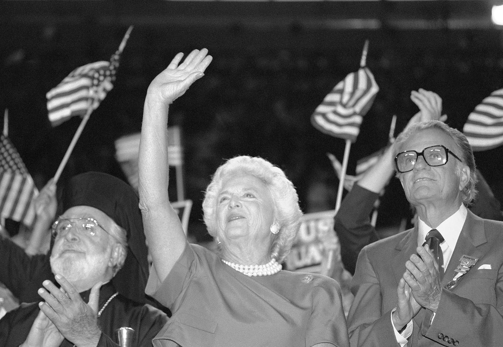 . Barbara Bush cheers and waves to her husband George with Bill Graham in New Orleans at the Republican National Convention, Aug. 18, 1988. (AP Photo/Tannen Maury)