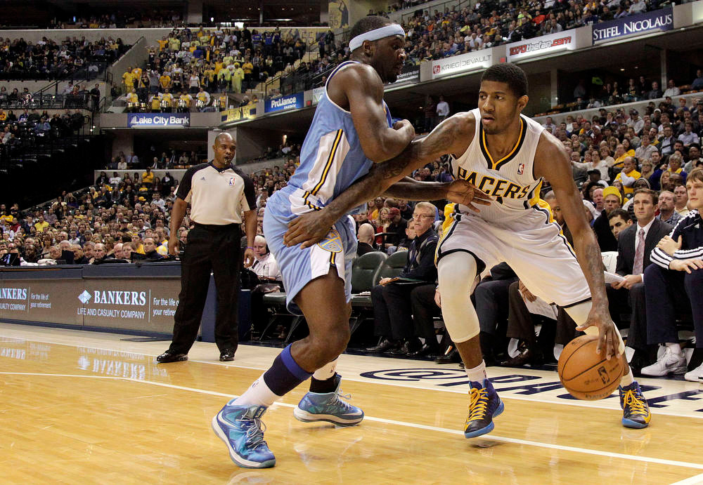 . Indiana Pacers forward Paul George, right, goes around Denver Nuggets guard Ty Lawson during the second half of an NBA basketball game in Indianapolis, Friday, Dec. 7, 2012. The Nuggets won 92-89. (AP Photo/AJ Mast)