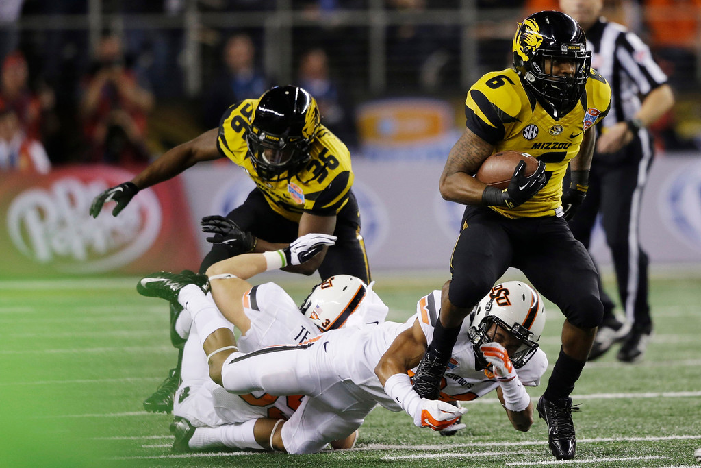 . Missouri running back Marcus Murphy (6) breaks a tackle-attempt by Oklahoma State cornerback Miketavius Jones (24) during the first half of the Cotton Bowl NCAA college football game on Friday, Jan. 3, 2014, in Arlington, Texas. (AP Photo/Tim Sharp)