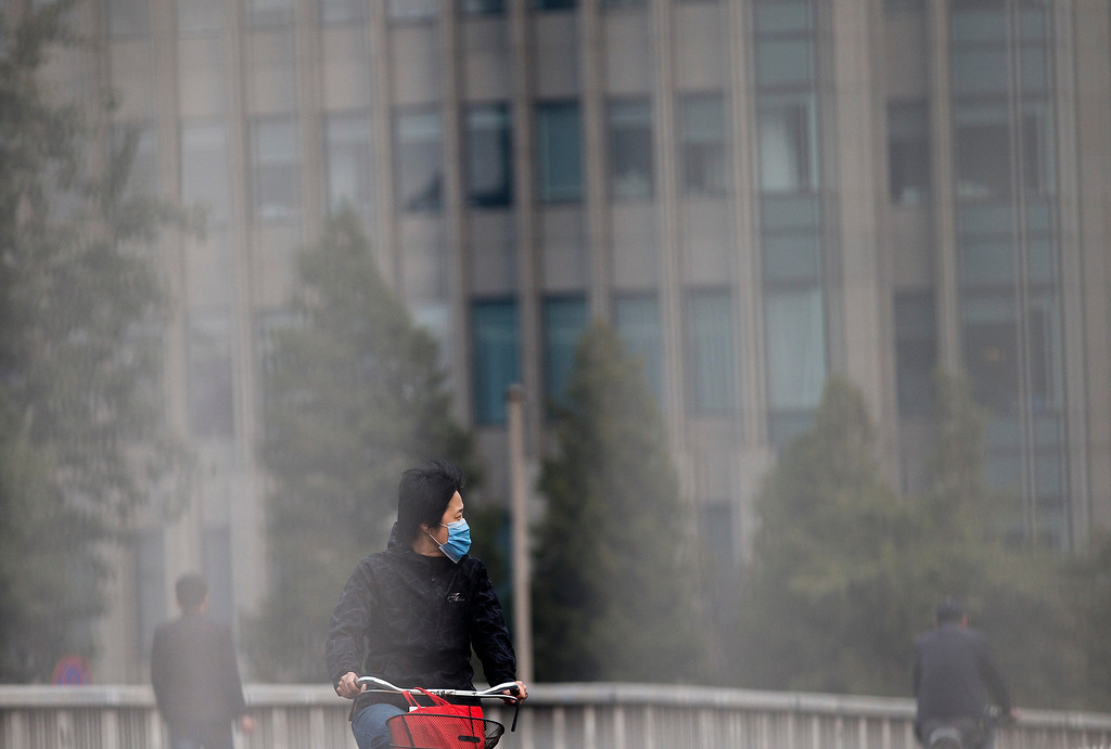. A woman wearing a face mask looks at the traffic as she bicycles on a road in Beijing Tuesday, Oct. 22, 2013.  (AP Photo/Andy Wong)