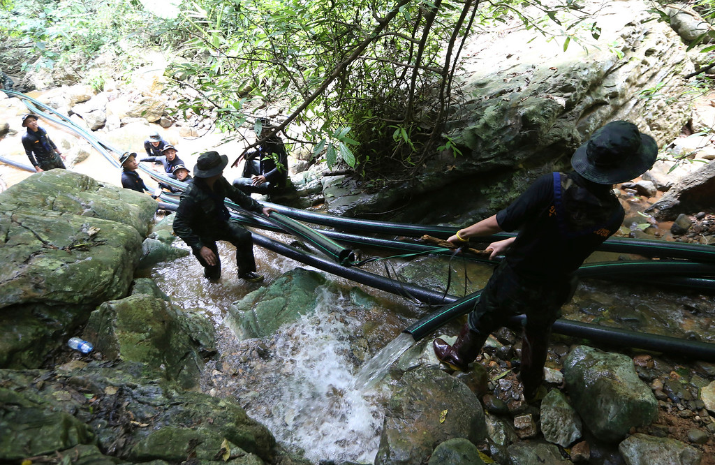 . Thai soldiers drag water pipes that will help bypass water from entering a cave where 12 boys and their soccer coach have been trapped since June 23, in Mae Sai, Chiang Rai province, in northern Thailand Saturday, July 7, 2018. Thai authorities are racing to pump out water from the flooded cave before more rains are forecast to hit the northern region. (AP Photo/Sakchai Lalit) (AP Photo/Sakchai Lalit)