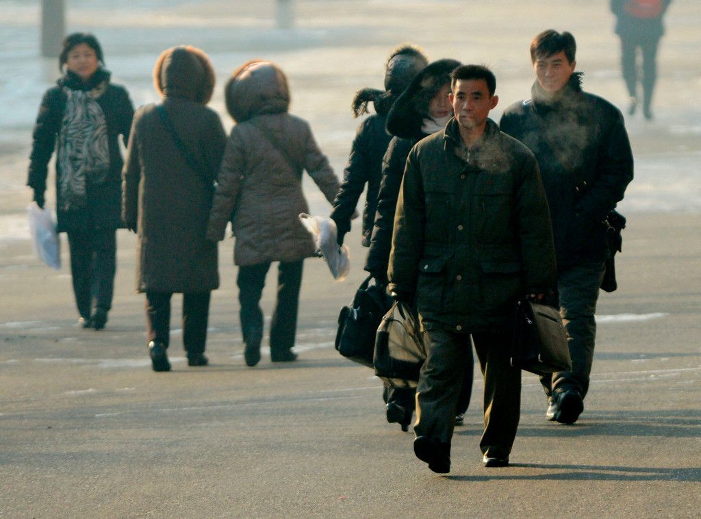 . North Koreans walk in Pyongyang, in this photo taken by Kyodo December 12, 2012. Isolated and impoverished North Korea launched its second long- range rocket of 2012 on Wednesday and may have finally succeeded in putting a satellite into space, the stated aim of what critics say is a disguised ballistic missile test.   REUTERS/Kyodo