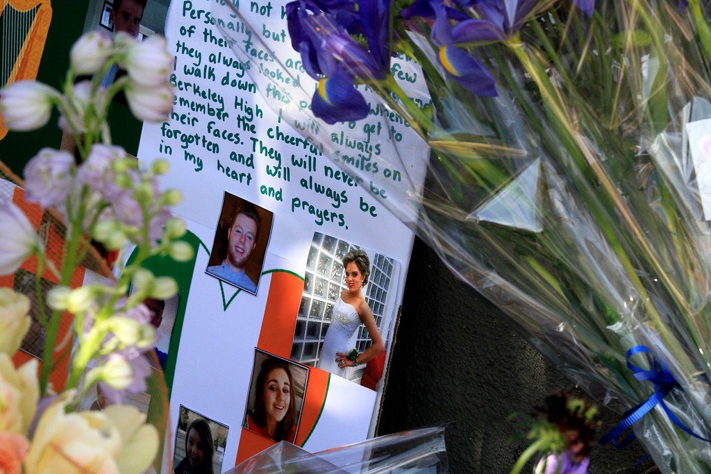 . A growing pile of flowers, photos, and cards sit on the sidewalk outside the residential apartment building in Berkeley, Calif. on Wednesday, June 17, 2015 where six people died and seven others were injured early Tuesday morning. (Laura A. Oda/Bay Area News Group)