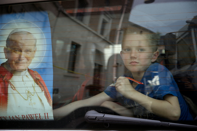 . A child stand in the rear of a van adorned with a picture of late Pope John Paul II in Rome, Saturday, April 26, 2014. Hundred thousands of pilgrims and faithful are expected to reach Rome to attend the scheduled April 27 ceremony at the Vatican in which Pope Francis will elevate in a solemn ceremony John XXIII and John Paul II to sainthood. (AP Photo/Gregorio Borgia)