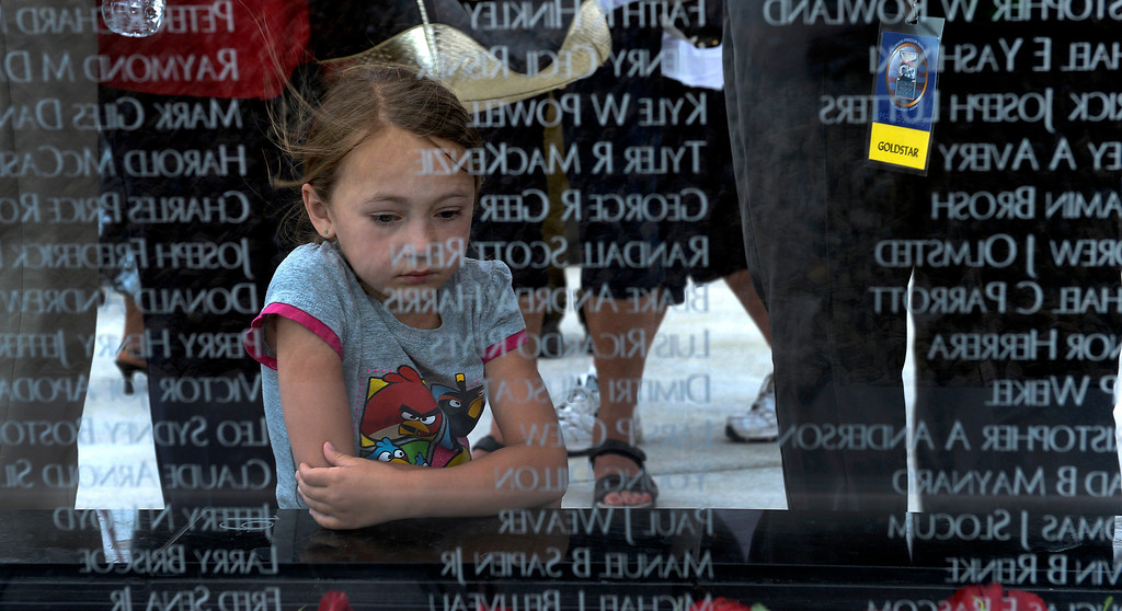. Cameron Hood, 6, reflects as she kneels down at the glass wall after finding her friend Ryan Baum on the glass after the dedication May 26, 2013 in Aurora. Ryan was in the Iraq war. The memorial was funded through a radio blitz drive last year by KEZW. The memorial is a 21 glass panel and bears the names of nearly 6,000 Coloradans killed or MIA in all wars. (Photo By John Leyba/The Denver Post)