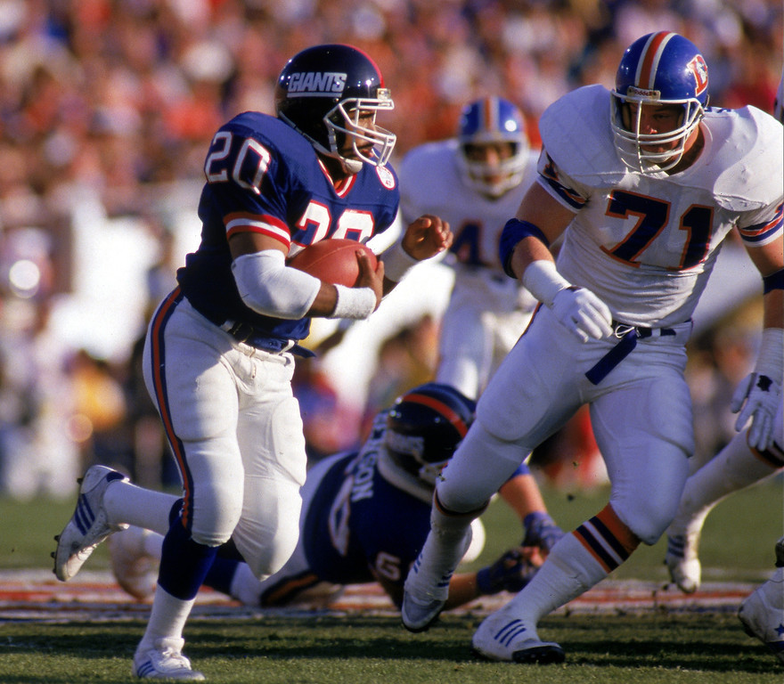 . Running back Joe Morris #20 of the New York Giants carries the ball against nose tackle Greg Kragen #71 of the Denver Broncos during Super Bowl XXI at the Rose Bowl. (Photo by George Rose/Getty Images)