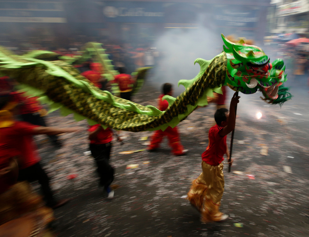 . Firecrackers explode as dragon and lion dancers perform in front of a grocery store in celebration of Chinese New Year at Manila\'s Chinatown district of Binondo, Philippines, Friday, Jan. 31, 2014. This year in the Chinese Lunar calendar is the Year of the Horse. (AP Photo/Bullit Marquez)