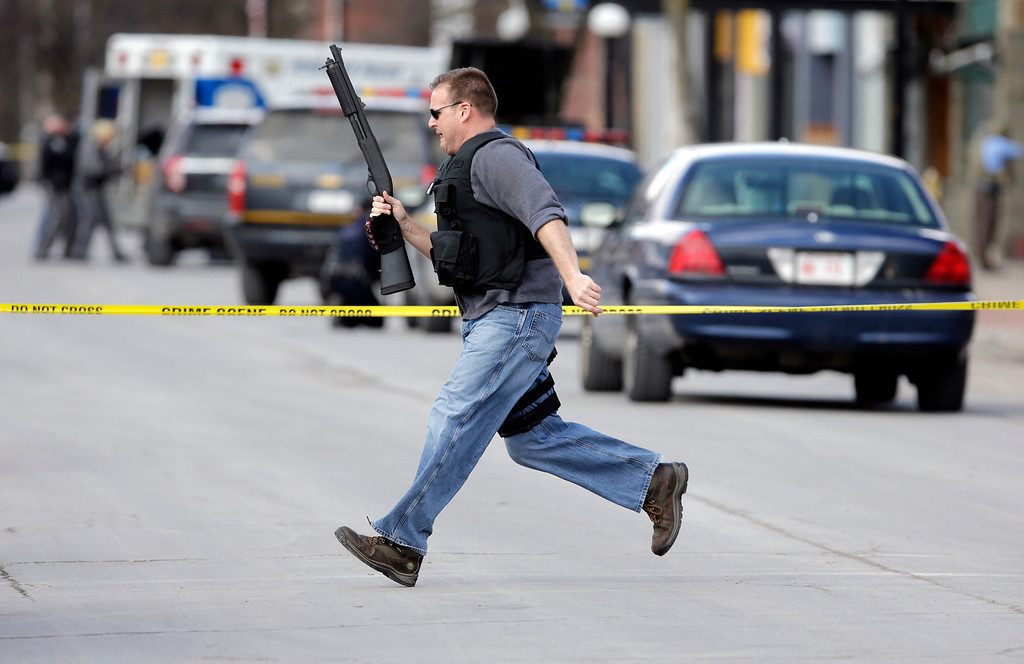. Law enforcement officers run for cover along Main Street  in Herkimer, N.Y., when shots were fired while they were searching for a suspect in two shootings that killed four and injured at least two on, Wednesday, March 13, 2013. Authorities were looking for 64-year-old Kurt Meyers, said Herkimer Police Chief Joseph Malone. Officials say guns and ammunition were found inside his Mohawk apartment after emergency crews were sent to a fire there Wednesday morning.  (AP Photo/Mike Groll)
