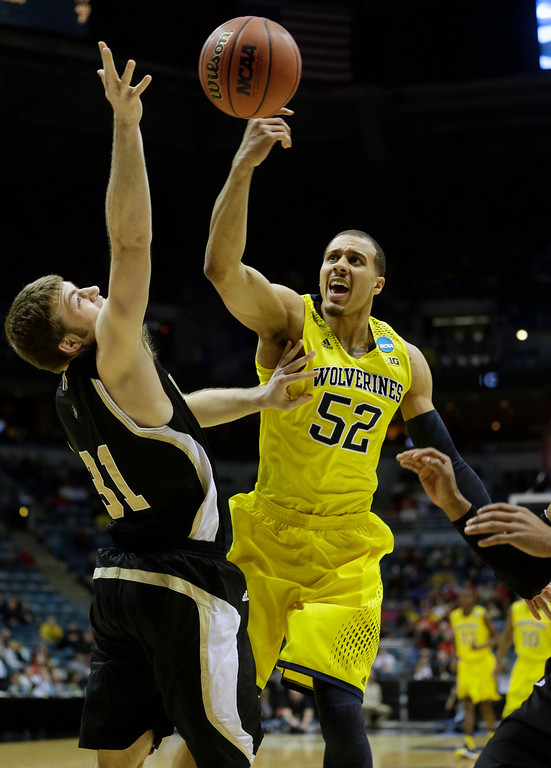 . Michigan forward Jordan Morgan (52) and Wofford forward C.J. Neumann (31) battle for a rebound during the first half of a second round NCAA college basketball tournament game Thursday, March 20, 2014, in Milwaukee. (AP Photo/Morry Gash)