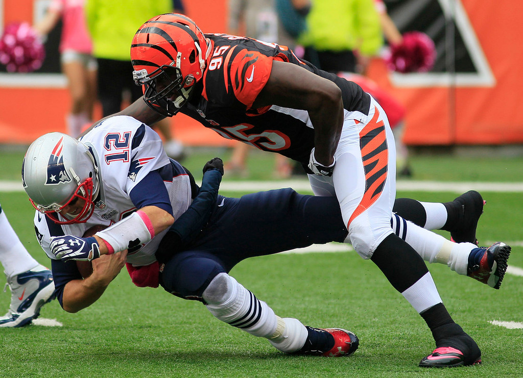 . New England Patriots quarterback Tom Brady (12) is sacked by Cincinnati Bengals defensive end Wallace Gilberry (95) in the first half of an NFL football game, Sunday, Oct. 6, 2013, in Cincinnati. (AP Photo/Tom Uhlman)