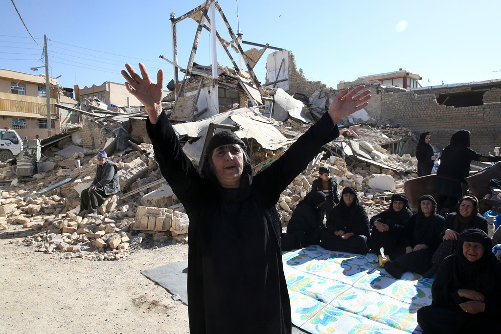 . A woman mourns at an earthquake site in Sarpol-e-Zahab in western Iran, Tuesday, Nov. 14, 2017. Rescuers are digging through the debris of buildings felled by the Sunday earthquake in the border region of Iran and Iraq. (AP Photo/Vahid Salemi)