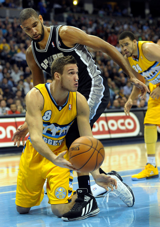 . Denver forward Danilo Gallinari (8) went to the floor to control a rebound in front of Spurs forward Tim Duncan (21) in the first half. The Denver Nuggets defeated the San Antonio Spurs 112-106 at the Pepsi Center Tuesday night, December 18, 2012. Karl Gehring/The Denver Post