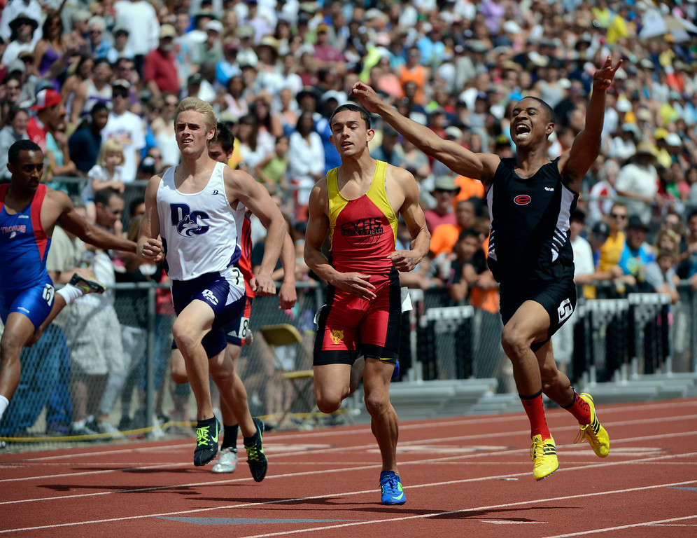 . Marcus Harris, right, of Eaglecrest High School, celebrates as he crosses the finish line first to edge out competitors, Tanner Townsend, Castle View High School, center, and Trey Smith, Douglas County High School, left, to win the boys 5A 100 meter dash at the Colorado State Track and Field Championships at Jeffco Stadium, Saturday morning, May 18, 2013.   (AP Photo/The Denver Post, Andy Cross)