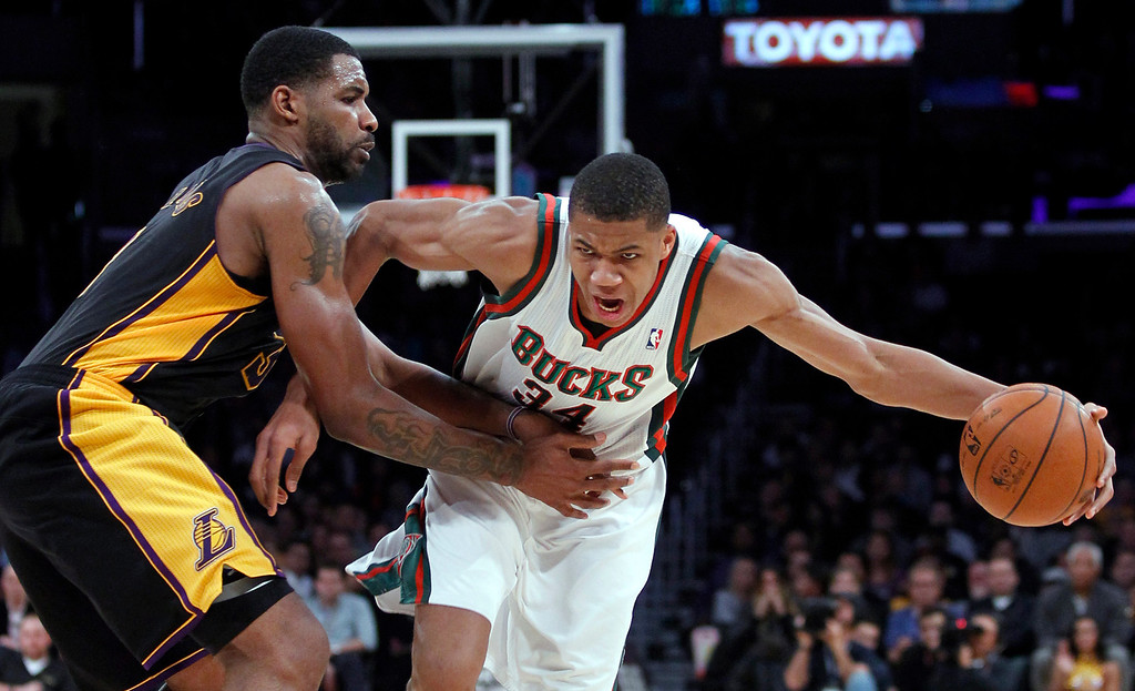 . Milwaukee Bucks shooting guard Giannis Antetokounmpo, right, drives against Los Angeles Lakers forward Shawne Williams during the second half of an NBA basketball game Tuesday, Dec. 31, 2013, in Los Angeles. The Bucks won 94-79. (AP Photo/Alex Gallardo)