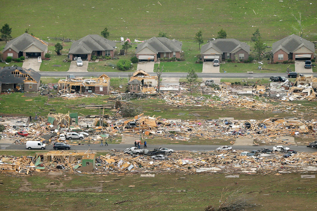 . A row of lightly damages houses, top, face destroyed homes in a Vilonia, Ark., neighborhood Monday, April 28, 2014 after a tornado struck the town late Sunday, killing at least 16 people.   (AP Photo/Danny Johnston)