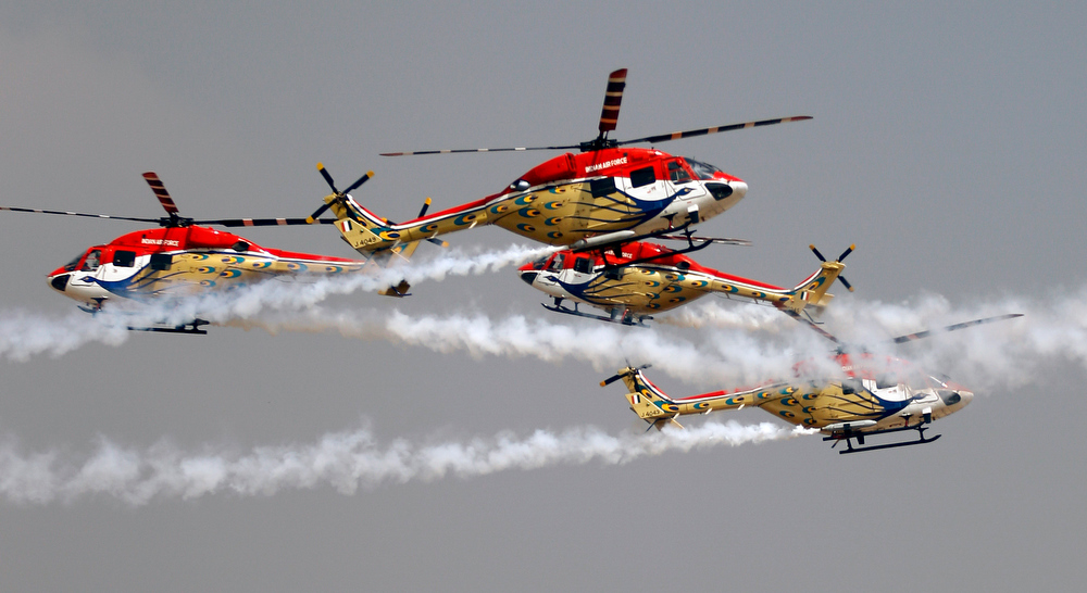 Description of . Indian Air Force helicopters cross paths while performing an aerobatic flight on the second day of the Aero India 2013 at Yelahanka air base in Bangalore, India, Thursday, Feb. 7, 2013. More than 600 aviation companies along with delegations from 78 countries are participating in the five-day event that started Wednesday. (AP Photo/Aijaz Rahi)