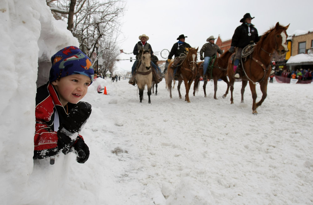 . STEAMBOAT SPRINGS, CO - FEBRUARY 09:  Nikolas Keyek, 4, of Steamboat Springs, gets a front row seat from inside a snow sculpture as horses head down Lincoln Street during the Street Events at the 95th Annual Steamboat Springs Winter Carnival on February 9, 2008 in Steamboat Springs, Colorado. Hosted by the Steamboat Springs Winter Sports Club the winter carnival is an annual competition featuring racing, ski jumping, various snow-related events held on the main street and the Lighted Man. Started in 1914 and held for several days in February in northwest Colorado, the town of Steamboat Springs is taken over by snow lovers, ranchers, cowboys, the young and old who come together to show visitors how winter is celebrated.  (Photo by Doug Pensinger/Getty Images)