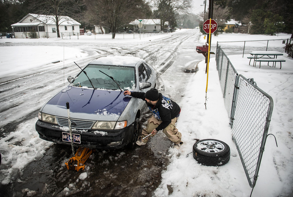 . Phil Giordano changes the bald tires on his car along snowy Center St. in the Massey Hill community in Fayetteville, N.C., Thursday morning, Feb. 13, 2014.  A major winter storm Wednesday brought a mixture of snow, sleet and freezing rain to North Carolina. (AP Photo/The Fayetteville Observer,  James Robinson)