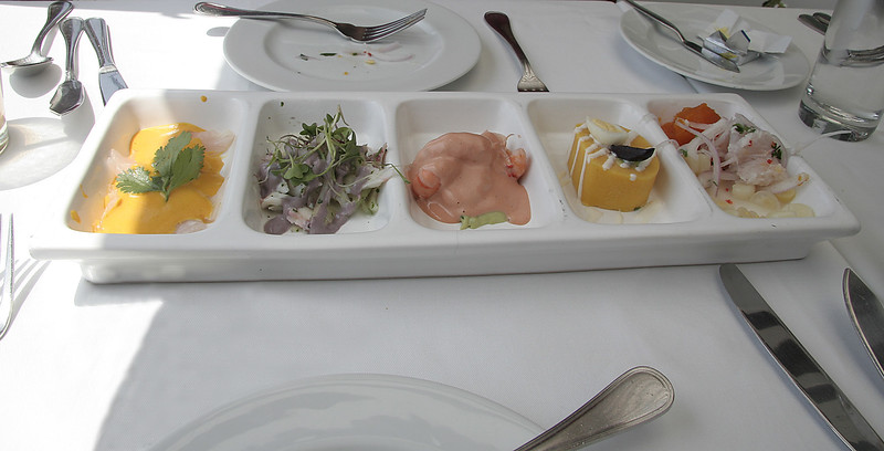 Un plato de piqueo. Left to right are:    *Tiradito - finely sliced ceviche (fish) without the onions  *Pulpo a la Oliva - braised baby octopus in a white wine/fish broth tossed with purple olive mayonnaisse  *Langostinos - prawns with sauce  *Causita - tuna tartare in a cylinder of mashed potatoes  *Ceviche - lime denatured/marinated fish (lenguado)