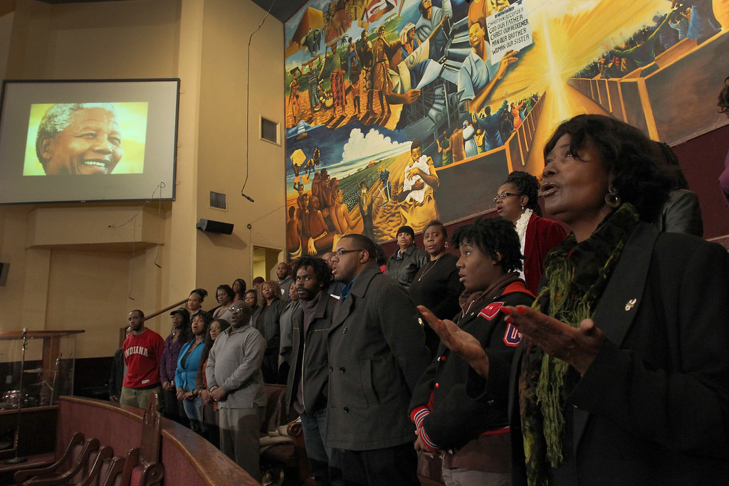 . LOS ANGELES, CA - DECEMBER 4:  Minister Kimberly Binion (R) and other members of the First AME Church Freedom Mass Choir sing the South African National Anthem in honor of the late former South African President and anti-apartheid leader Nelson Mandela, whose image appears on the left, during choir rehearsal on December 5, 2013 in Los Angeles, California. First AME Church of Los Angeles was the site of Nelson Mandela\'s first visit to Los Angeles after he was freed from prison. The Freedom Mass Choir sang for him then and during later visits to the U.S. Incumbent South African President Jacob Zuma announced earlier today that Mandela has died at the age of 95.   (Photo by David McNew/Getty Images)