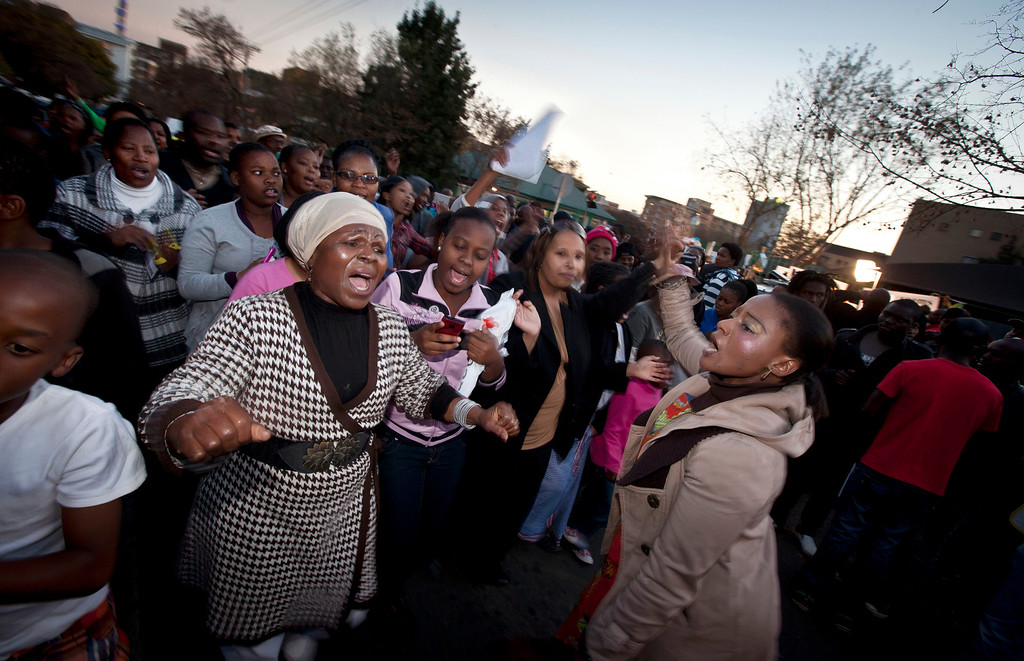 . A community group from Pretoria sing hymns and songs from the apartheid era, to show their appreciation and support for former South African President Nelson Mandela, on the street outside the Mediclinic Heart Hospital where he is being treated in Pretoria, South Africa Tuesday, June 25, 2013. South Africa\'s president Jacob Zuma on Tuesday urged his compatriots to show their appreciation for Nelson Mandela, who is in critical condition in a hospital, by marking his 95th birthday next month with acts of goodness that honor the legacy of the anti-apartheid leader. (AP Photo/Ben Curtis)